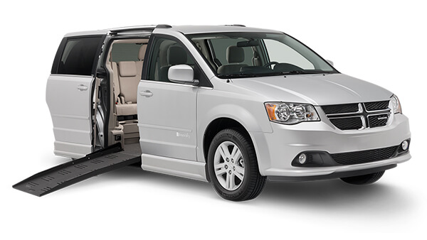 Silver Braunability van with left side door opened and mobility wheelchair ramp extending to the floor