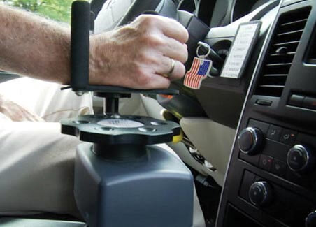 person using electronic hand controls on a vehicle