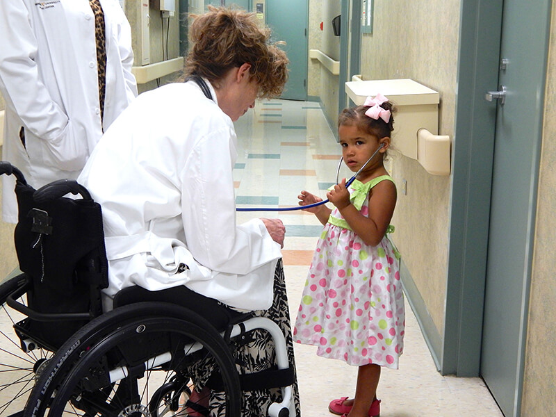 female doctor in wheelchair showing young girl stethoscope