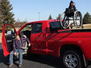 Red pickup truck with hoist lift in bed of truck and person sitting on a turning seat