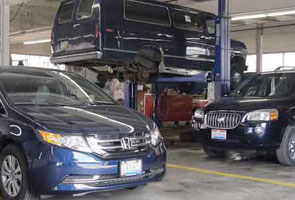 A blue Honda, commercial van, and SUV in a garage