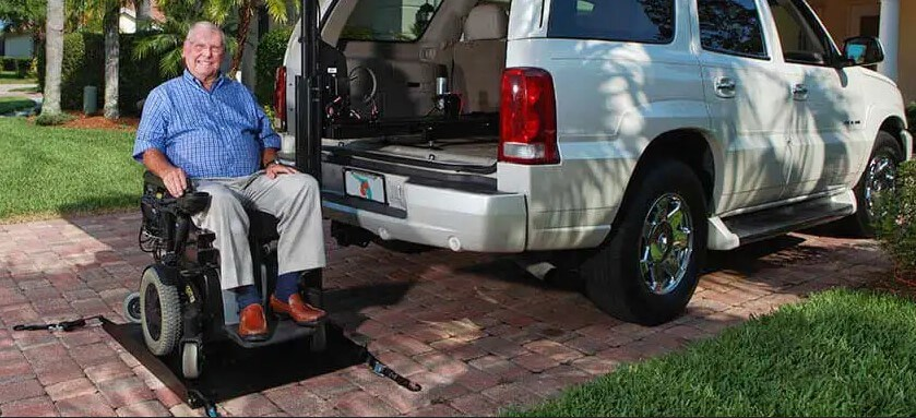 Man sitting on a wheelchair lift attached to a white SUV parked on a cobblestone driveway