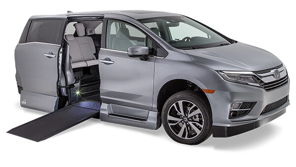Gray Honda Odyssey with side entry door open and a wheelchair ramp extending to the ground